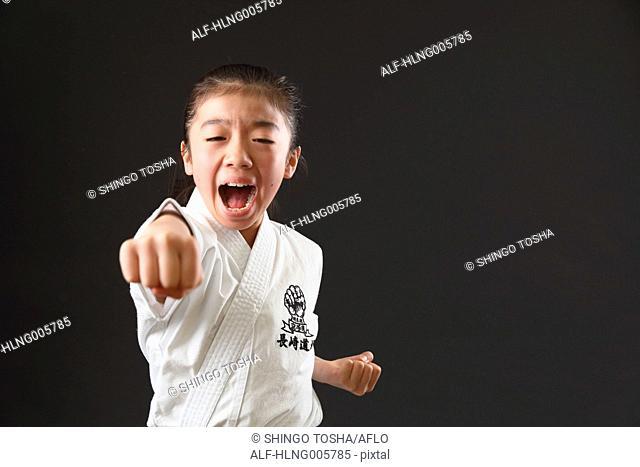 Japanese kid in karate uniform on black background