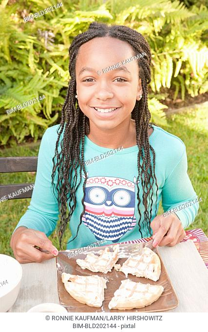 African American girl eating waffle in backyard