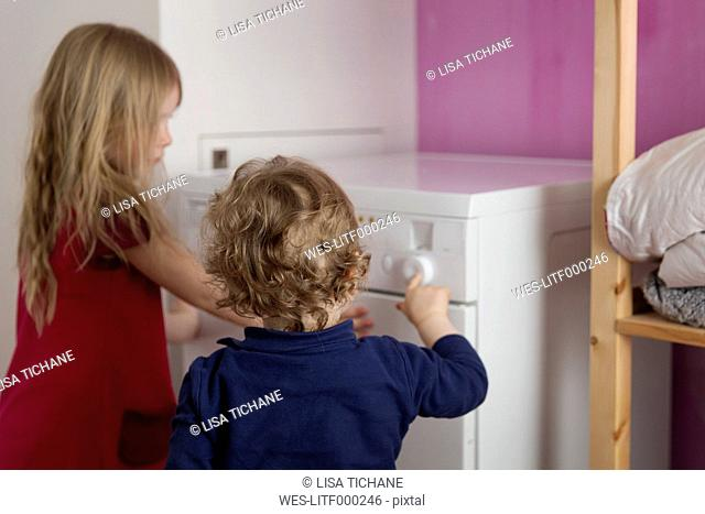 Back view of little boy switching on tumble dryer