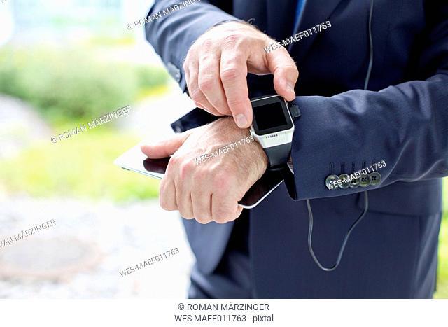 Close-up of businessman using smartwatch