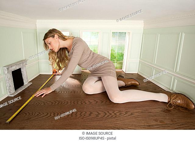 Young woman in small room measuring the floor