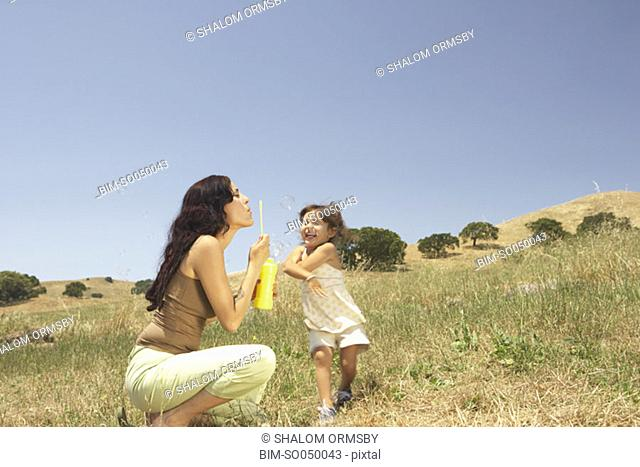 Mother and daughter blowing bubbles outside