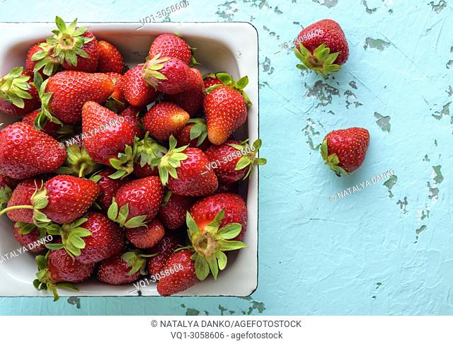 fresh ripe red strawberry in a white square plate, top view