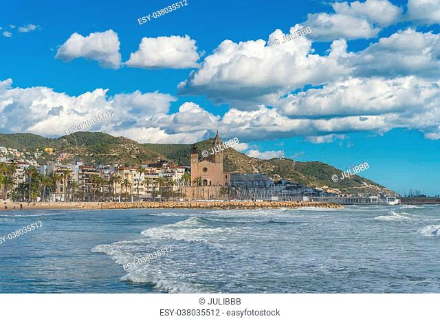 Far away view of large church surrounded by various hotels and vacation resorts near coast line under blue sky and white clouds in Sitges, Spain