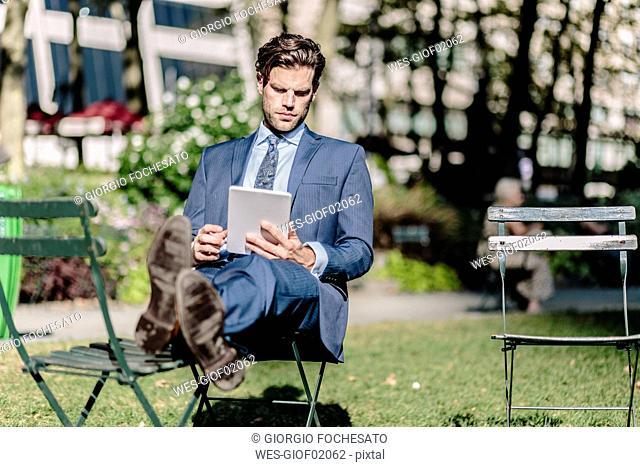 Businessman in Manhattan sitting on garden chair using digital tablet with feet up