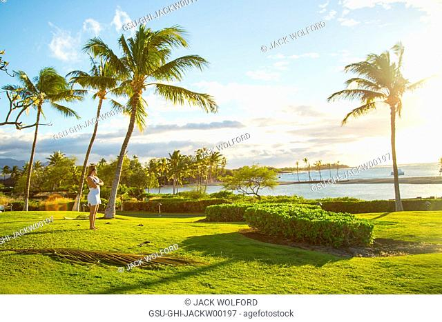 Mid-Adult Woman Looking out to Pacific Ocean from Green Lawn Amongst Coconut Trees, Hawaii, USA