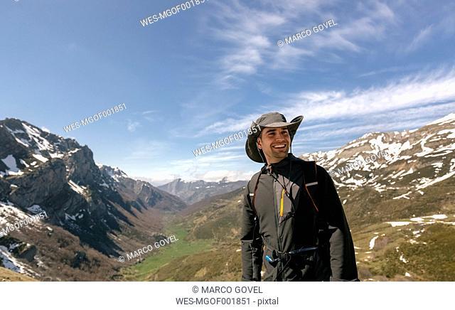 Spain, Asturias, Somiedo, smiling man hiking in mountains