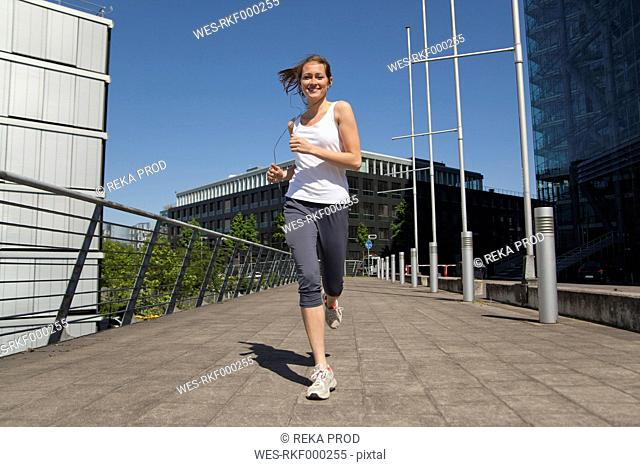 Germany, North-Rhine-westphalia, Duesseldorf, Young woman Jogging, smiling, portrait