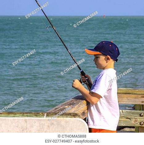 A little boy fishing in the ocean wearing baseball cap