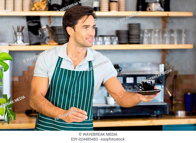 Waiter offering a cup of coffee