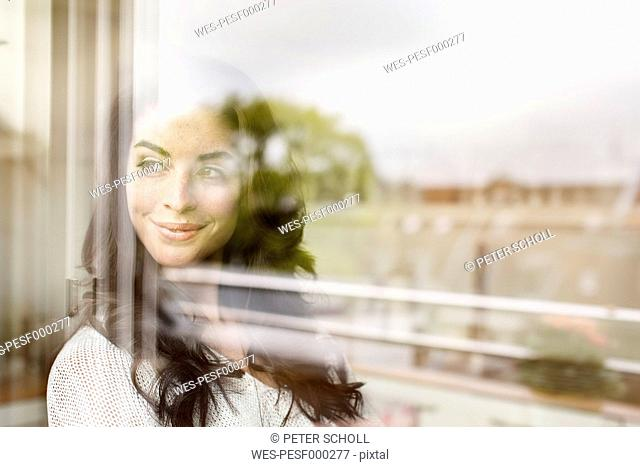 Smiling young woman looking out of window