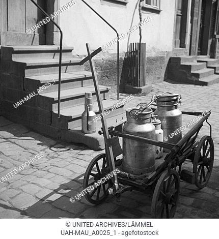 Ein Handkarren mit Milchkannen steht in einer Gasse in Deutschland, 1930er Jahre. A push cart with milk cans on a cobblestone lane in Germany, 1930s