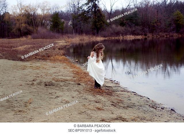 Girl (4-5) in white dress on lakeshore