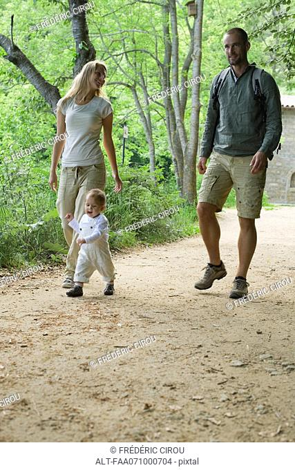 Parents hiking in woods with toddler