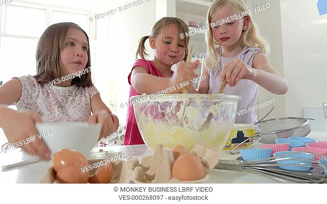 Time lapse sequence of three young girls adding ingredients into glass mixing bowl to make cake.Shot on Canon 5D Mk2 at a frame rate of 25fps