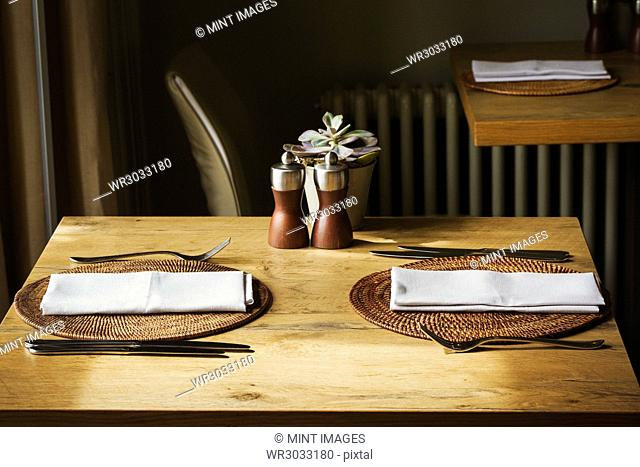 Wooden table set with place mats, napkins and cutlery in a restaurant