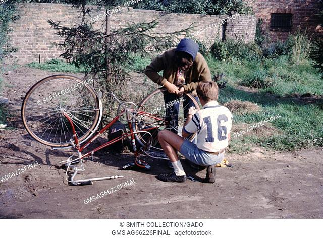 A young adult biker fixing the rear tire of a bike at the side of the road with the help of another man, 1966