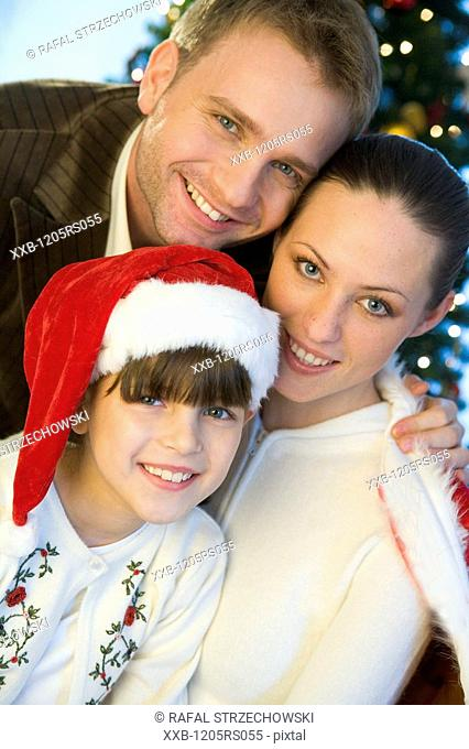 portrait of a family next to christmas tree
