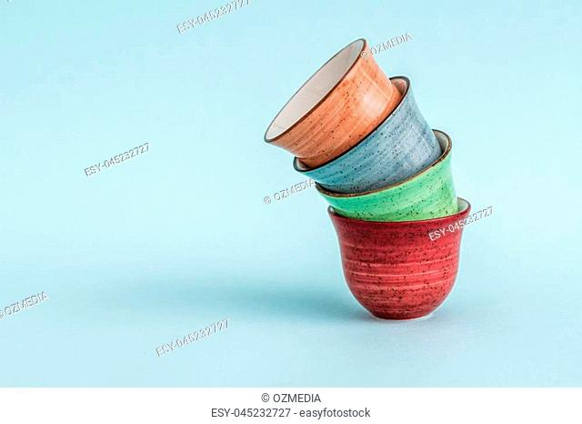 Colorful ceramic Espresso cups on green background
