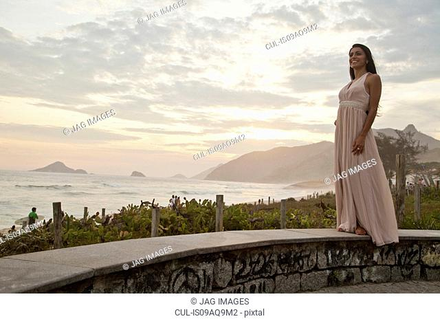 Mid adult woman standing on wall by ocean