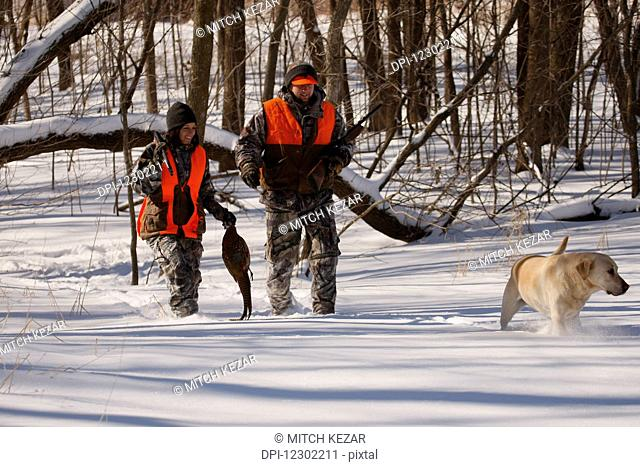 Male and Female Pheasant Hunters In Winter With Yellow Lab