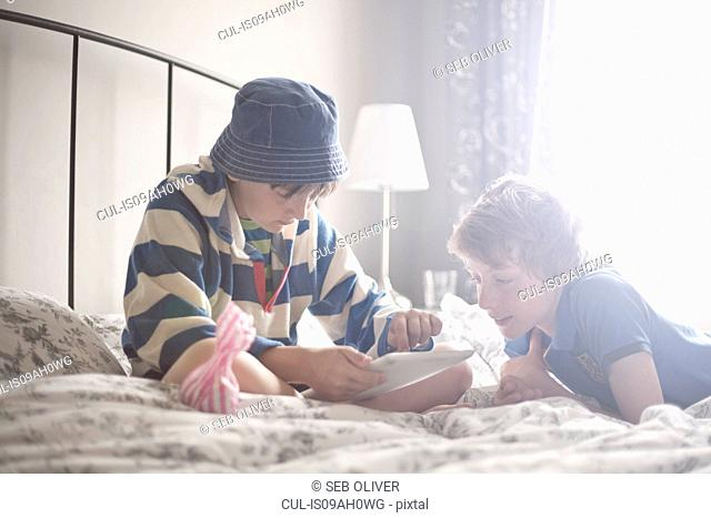Two brothers relaxing on bed using digital tablet