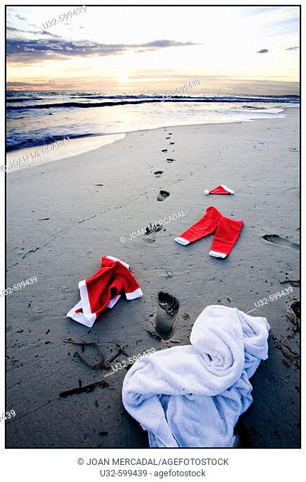 Father christmass clothes left on the beach, and foot steps towards the sea