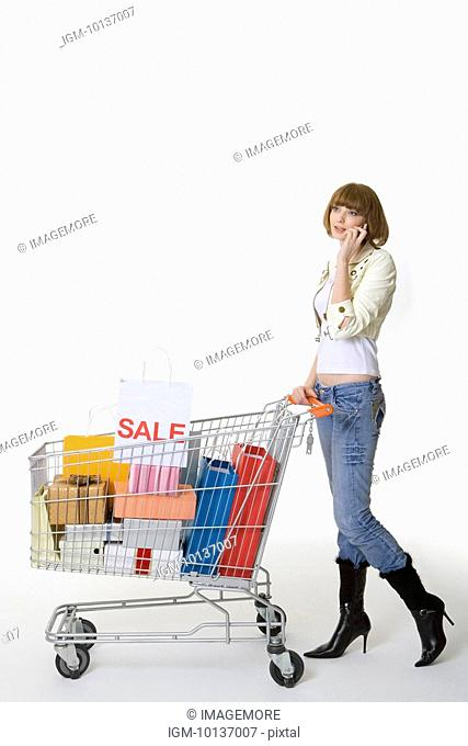 Teenage girl on the phone pushing shopping cart