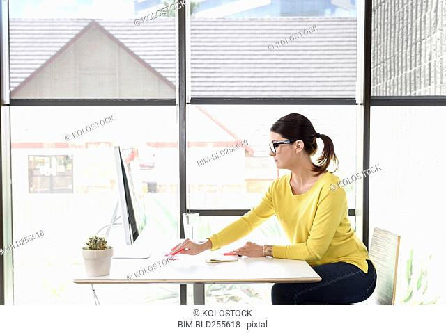 Caucasian woman writing on adhesive notes at desk