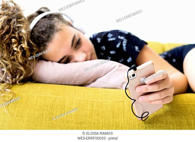 Girl lying on the couch at home listening music with headphones and smartphone