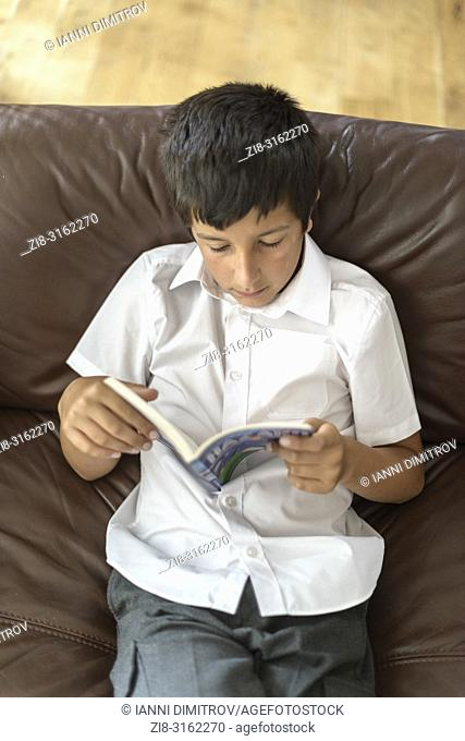 Surrey,UK-Young boy in school uniform reading at home-elevated view