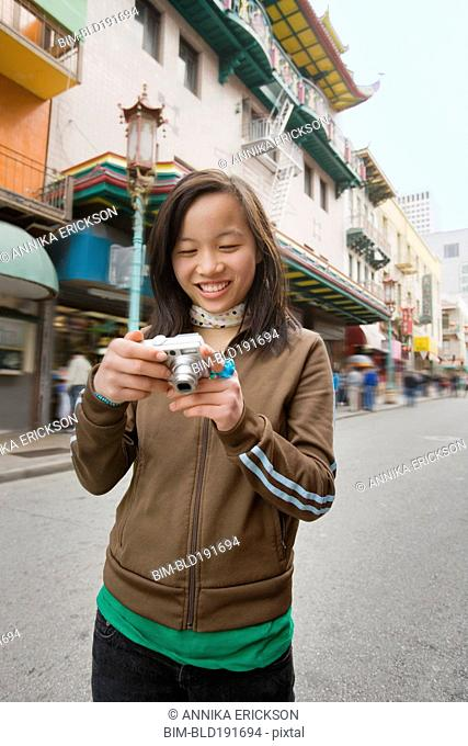 Chinese girl holding digital camera on urban street