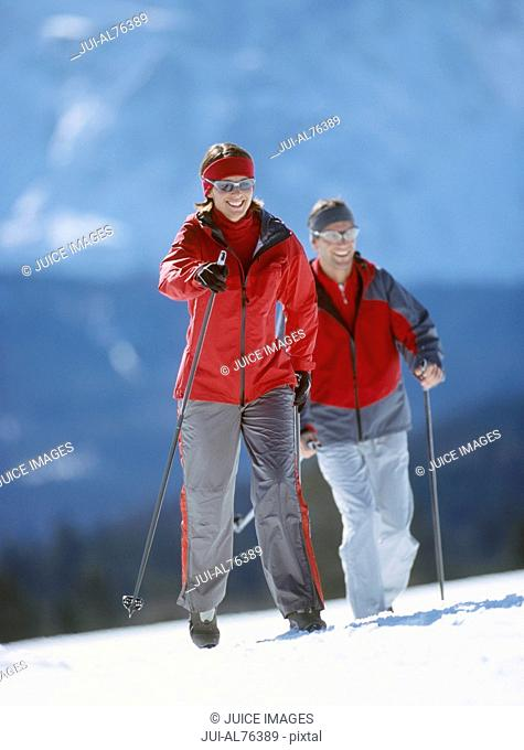 View of a young couple cross-country skiing in winter setting