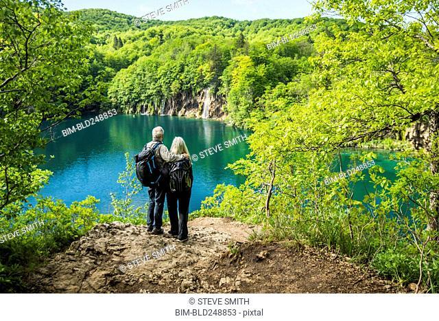 Older Caucasian couple admiring waterfall