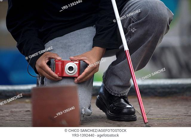 A blind photographer takes pictures as he kneels