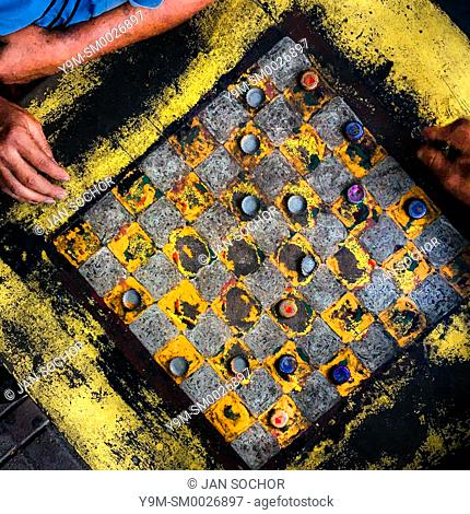 Hands of Salvadoran men are seen resting on the table while playing checkers on an outdoor checkerboard table in the park in San Salvador, El Salvador
