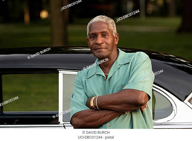 African man leaning on old-fashioned car