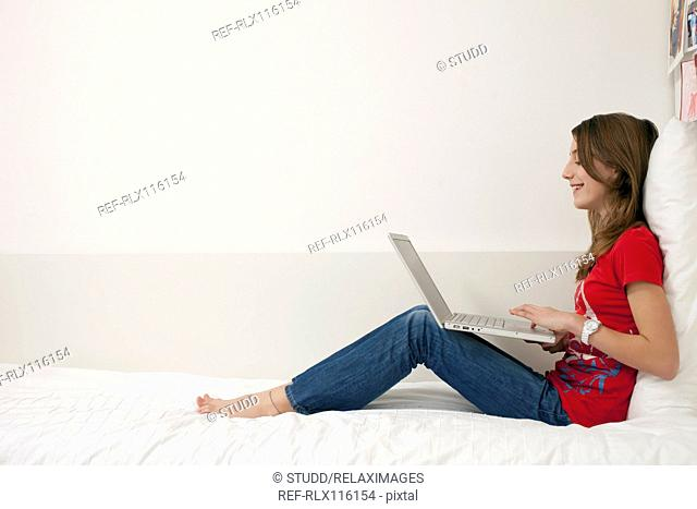 Girl sitting on bed working with laptop computer