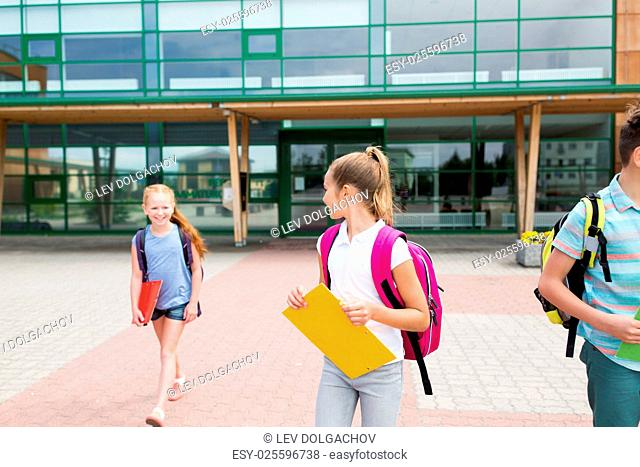 primary education, friendship, childhood, communication and people concept - group of happy elementary school students with backpacks and folders walking...