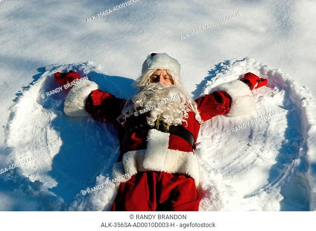 Santa making a snow angel in fresh snow