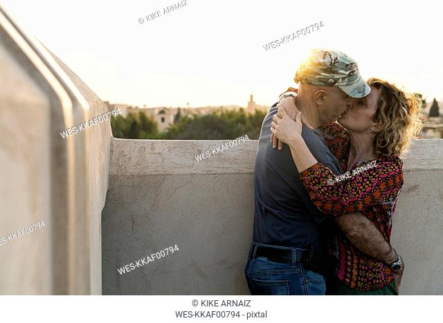 Morocco, Marrakesh, couple kissing at sunset