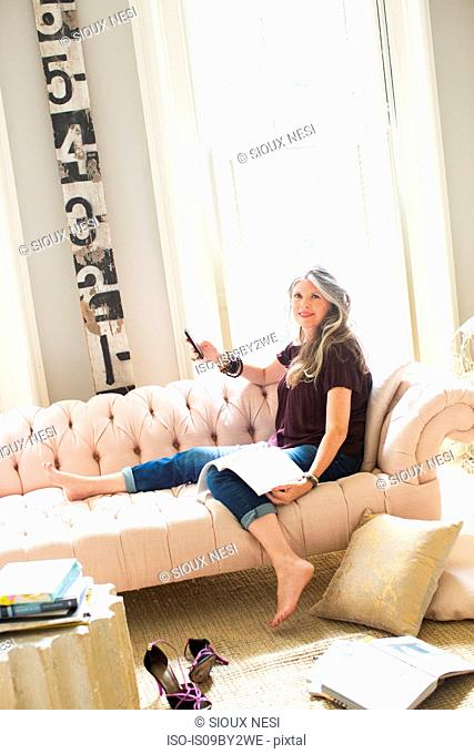 Stylish mature woman sitting on sofa holding smartphone, portrait