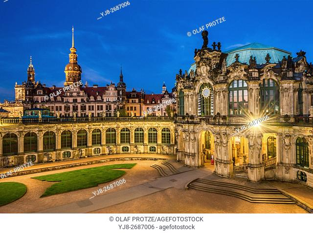 Bell Chime and entrance to the Procellain Collection at the Zwinger Palace at night, with the Dresden Castle in the background, Saxony, Germany