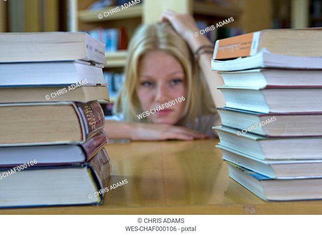 Germany, Baden-Wuertemberg, stressed young female student with stack of books in a library