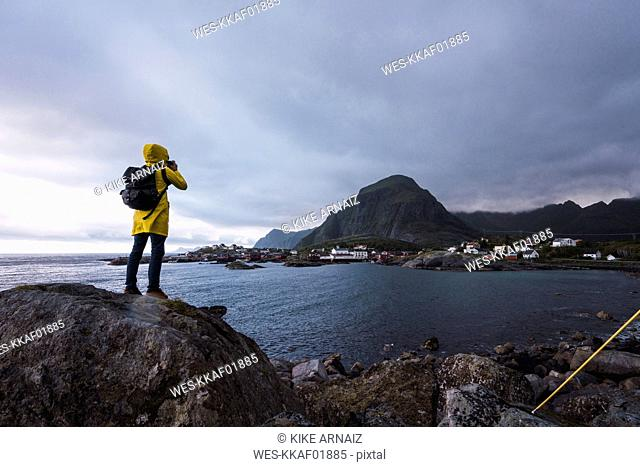 Norway, Lofoten, rear view of man standing on a rock at the coast taking a picture