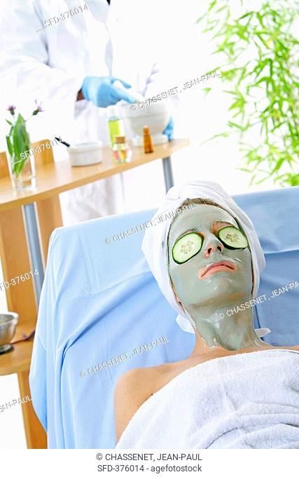 Woman with clay face mask and cucumber slices on her eyes