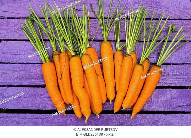 Fresh carrots on purple wooden table