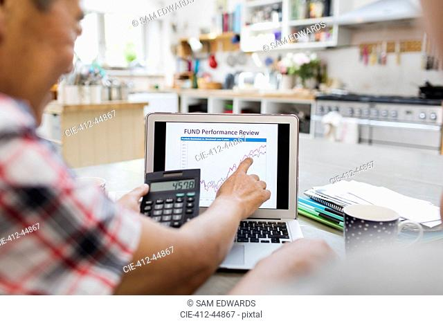 Senior man with calculator looking at investment chart on laptop