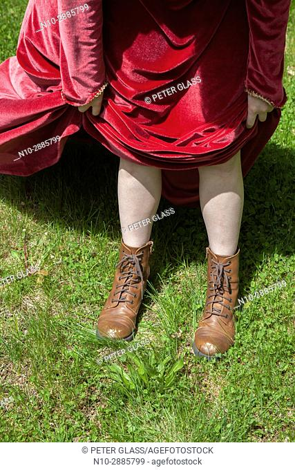 Young woman's legs wearing boots and a long red vintage dress