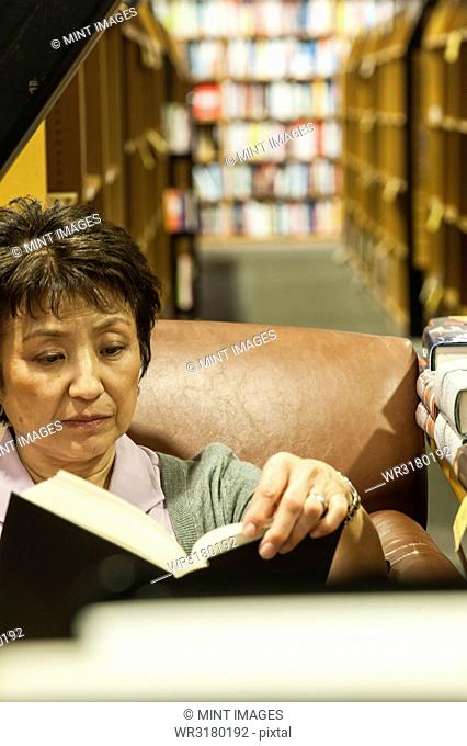 Asian American female browsing through books in a bookstore while sitting in a chair in front of a rack of books